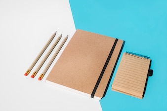 Pencil; closed notebook and spiral notepad on white and blue backdrop