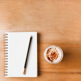 Pencil on closed white spiral notebook and coffee glass on wooden textured background