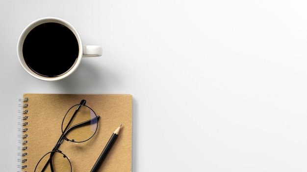 Pencil, coffee cup and diary book at white desk. - work from home concept.