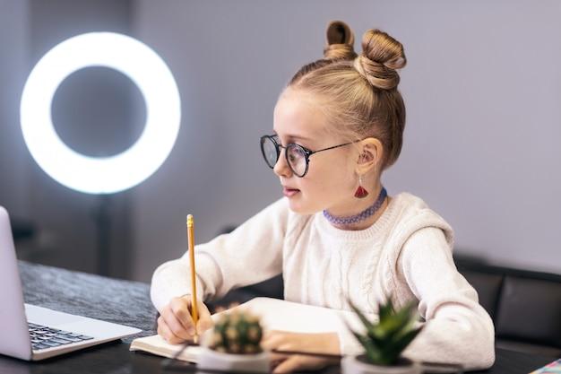 鉛筆。彼女の手に鉛筆を持っている白いセーターを着ているかわいい青い目の長い髪の少女