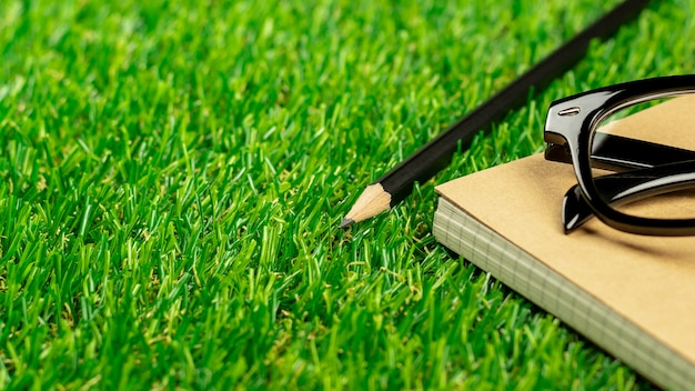 Pencil, diary book and a glasses on green grass lawn in the morning.