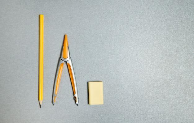 Карандаш, ластик и циркуль. плоская композиция из желтых офисных инструментов на сером фоне.