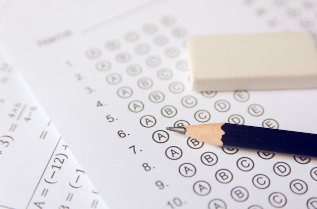 Pencil and eraser on answer sheets or standardized test form with answers bubbled. multiple choice answer sheet
