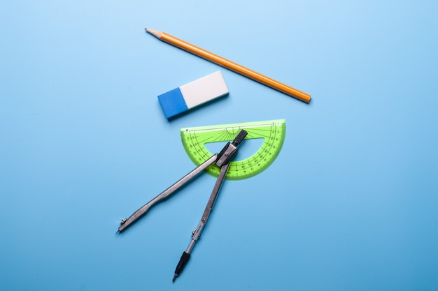 Pencil, eraser, ruler and compass on blue background