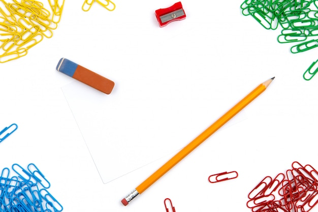 Pencil, eraser, sharpener, paper clips lie in different angles of the sheet on a white background. hero image and copy space.