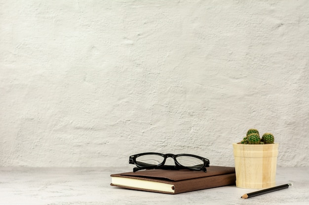 Pencil, glasses and a leather notebook on the desk with copy space. - office supplies or education concept.