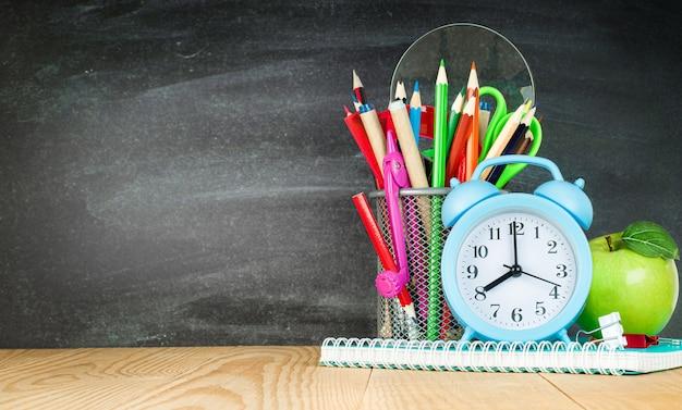 연필 홀더, 알람 시계 및 칠판 배경에 녹색 사과