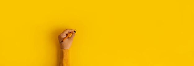 Карандаш в руке на желтом фоне, панорамный макет