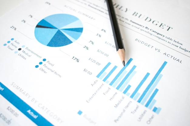 The pencil is placed on the financial graph of the businessman.