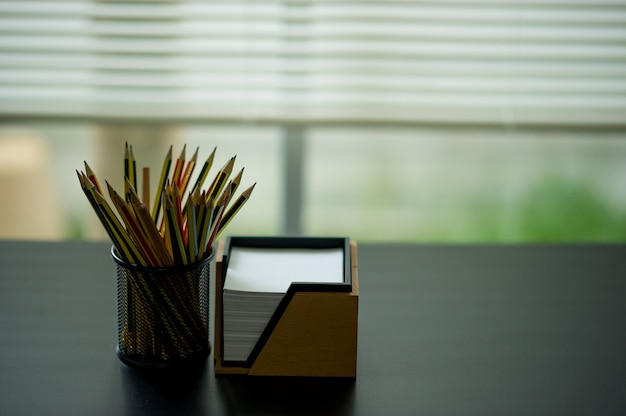 Pencil and note placed on the executive desk. placed by the window