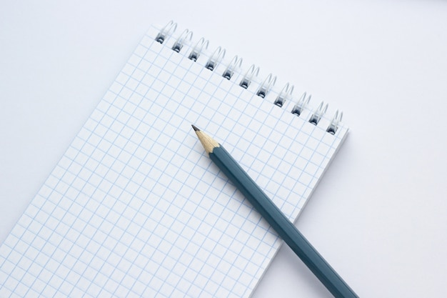 Pencil and notebook on white background, close-up