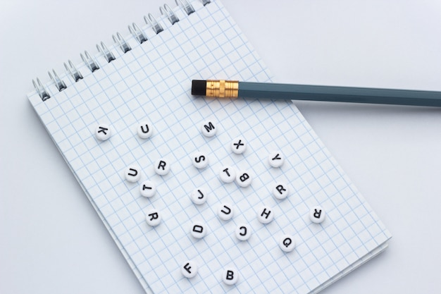 Pencil and notebook with letters on a white background, concept of writing a letter