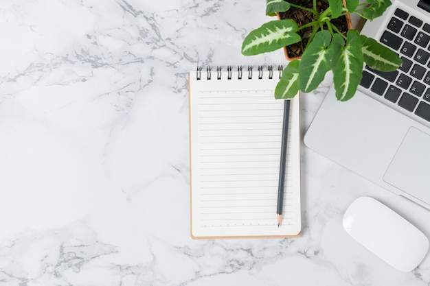 Карандаш на пустом блокноте с ноутбуком и мышью на фоне мраморного стола, вид сверху и пространство для копирования