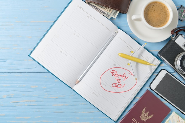 古い木の背景にヴィンテージカメラとスマートフォンでノートブックに鉛筆、旅行する準備をする