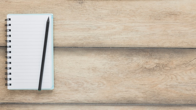 Pencil on opened notebook on wooden desk