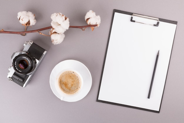 Pencil and paper on clipboard near camera, plant twig and cup