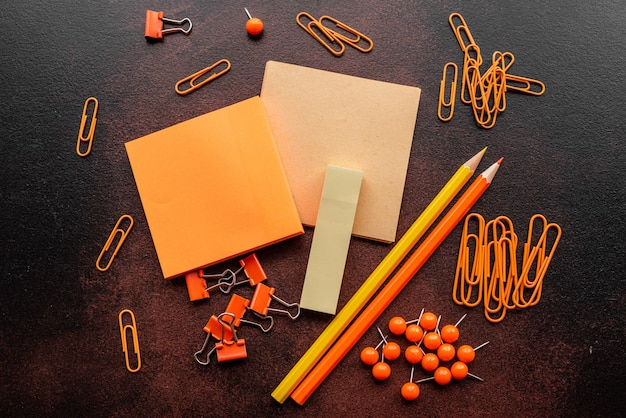 The pencil, paper clips and sheets for marks lie on a desktop