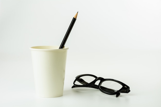 Pencil in a paper coffee cup and eyeglasses on white background.