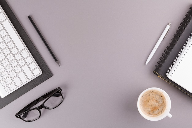 Pencil, pen and notebooks near keyboard, eyeglasses and cup