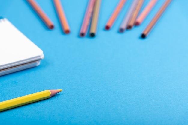 鉛筆とメモ帳で机の上の無地を指す鉛筆