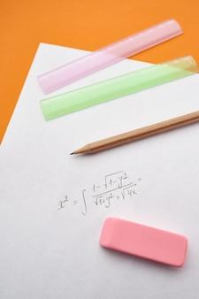 Лист бумаги, карандаш, линейка, резина, оранжевая стена. канцелярские товары, школьные или образовательные принадлежности, инструменты для письма и рисования