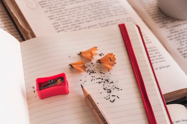 Pencil and sharpener on notepad and books