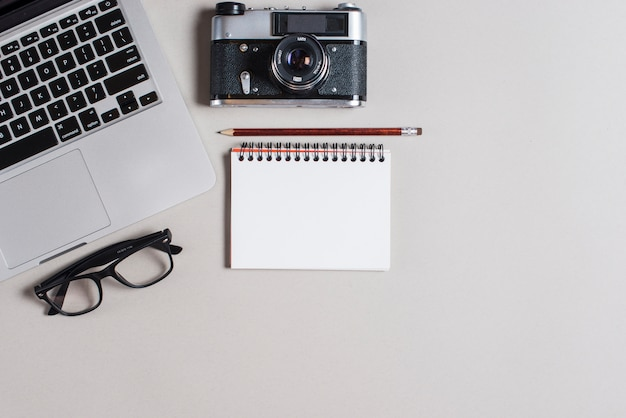 Pencil over spiral notepad with laptop; camera and eyeglasses on gray backdrop