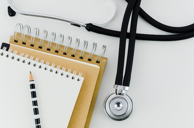 Pencil on the stack of spiral notepad with stethoscope on white backdrop