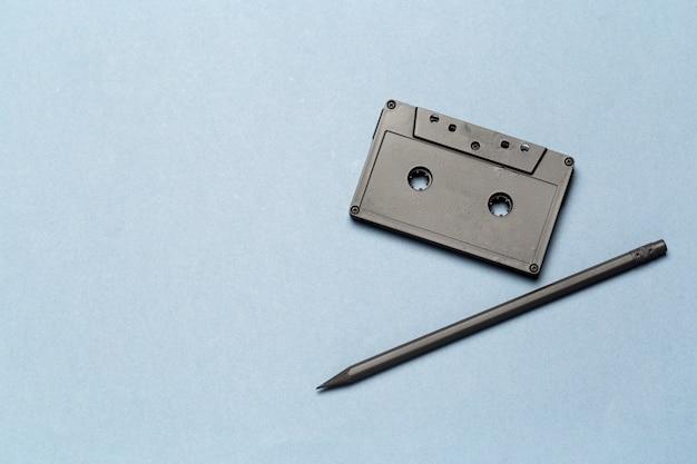 밝은 회색 배경에 테이프 카세트를 되 감는 연필 도구