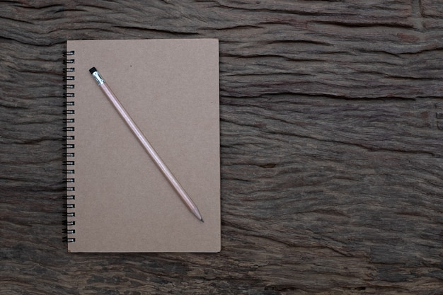 Pencil on top of book mockup on the old wood desk at the background, flat lay photo, top view