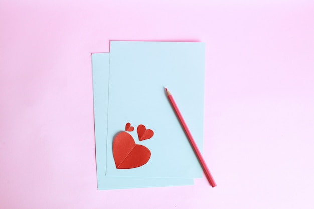 Pencil with red heart shape on white paper isolated on pink background