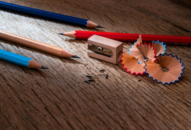 Pencil with sharpening shavings on old wooden texture background