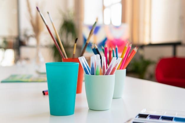 アートワークショップのテーブルの上のガラスの鉛筆とブラシ
