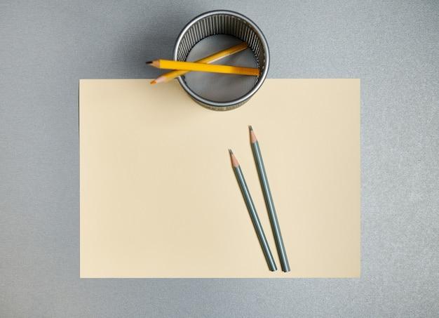 Карандаши и подставка для карандашей на желтой бумаге на сером фоне. плоская планировка. вид сверху