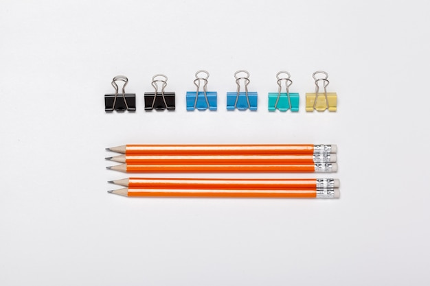 Pencils arranged in the row and paper clips