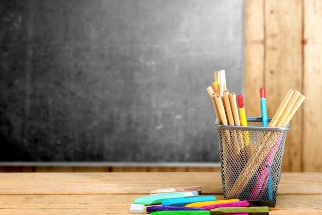Pencils in basket container and colorful crayons on the wooden table with blackboard