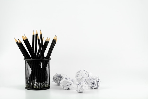Pencils in basket and crumpled paper ball on a white table