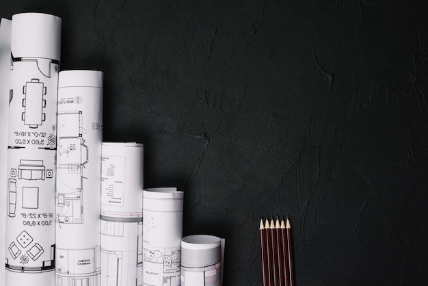 Pencils and blueprints on table