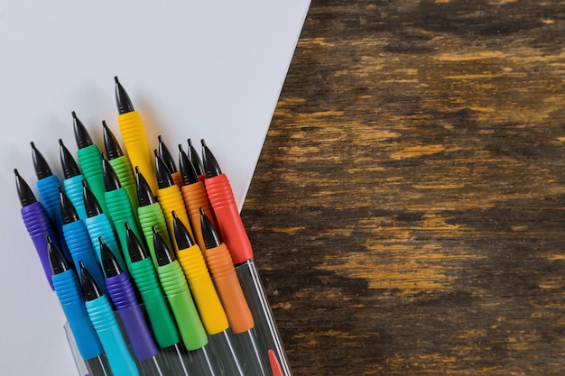 Pencils and drawing pad on wooden background. school stationery.