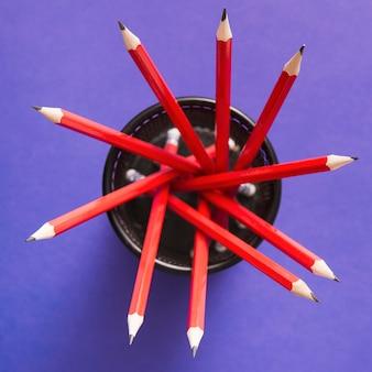 보라색 배경 위에 검은 홀더 안에 연필