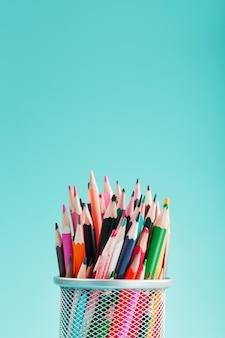 青い背景のガラスの異なる色の鉛筆。