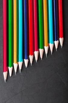 黒のテクスチャ背景に連続したさまざまな色の鉛筆。上面図