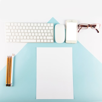 Pencils and paper near gadgets and glasses