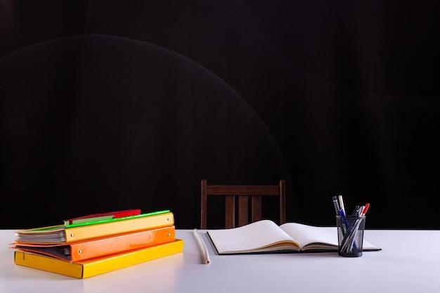 積み重ねられた本と開いたノートの横にある鉛筆ポット、背景に黒板のテクスチャーが付いた白い机の上の学用品。側面図、コピースペース。学習、教育の概念