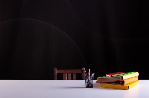 積み重ねられた本の横にある鉛筆ポット、背景に黒板のテクスチャーが付いた白い机の上の学用品。側面図、コピースペース。学習、教育の概念