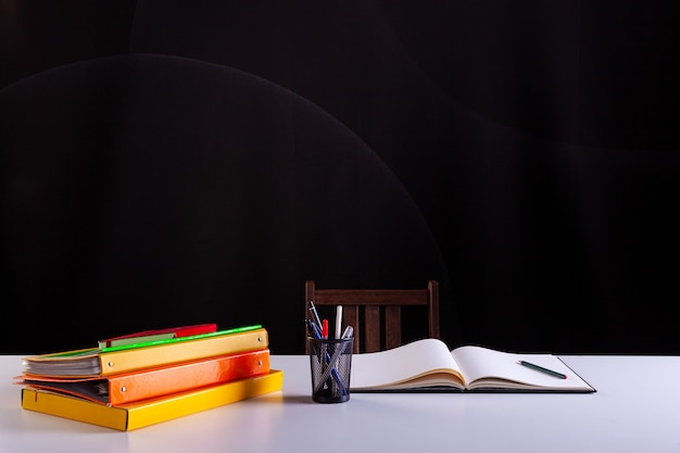 Pencils pot next to the stacked books and an open notebook , school supplies on white desk with blackboard texture in background. side view, copy space. learning, education concept