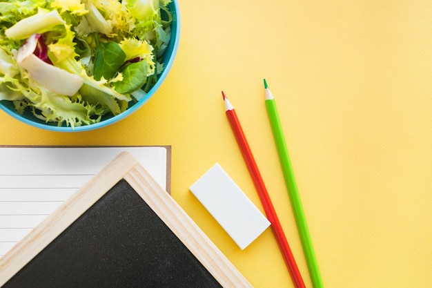 Pencils and rubber near blackboard and salad