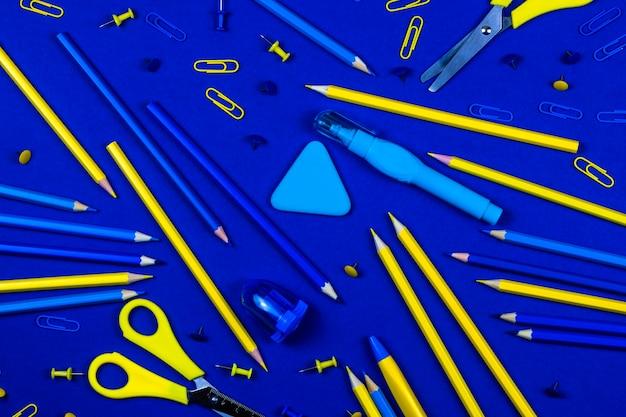 Карандаши, ножницы, скрепки и пуговицы синего и желтого цвета лежат на синем фоне.