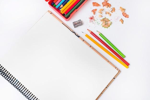 Pencils and sharpener near notebook