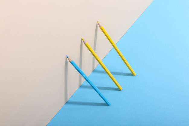 Pencils stand against the wall, casting a shadow, drawing geometric shapes.